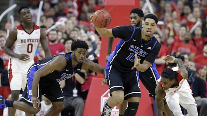 Duke's Jahlil Okafor (15) and Justise Winslow drive the ball up court as North Carolina State's Anthony Barber chases at right during the second half of an NCAA college basketball game in Raleigh, N.C., Sunday, Jan. 11, 2015. North Carolina State won 87-75. (AP Photo/Gerry Broome)