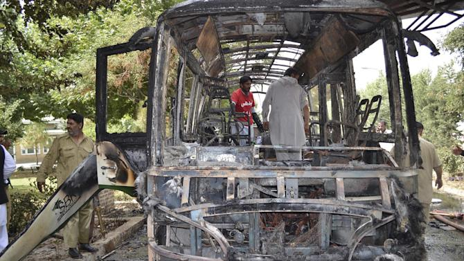 Pakistani volunteers collect body parts of victims of a bomb blast from the wreckage of a bus in Quetta, Pakistan, Saturday, June 15, 2013. A bomb tore through a bus carrying female university students in southwestern Pakistan Saturday, killing several, officials said. As family and friends gathered at the hospital another blast went off, followed by a flurry of bullets that sent bystanders running for cover. (AP Photo/Arshad Butt)