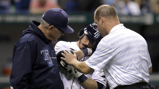 Tampa Bay Rays manager Joe Maddon, left, and a trainer, right, look at Will Rhymes after he was hit by an eighth-inning pitch from Boston Red Sox reliever Franklin Morales during a baseball game Wednesday, May 16, 2012, in St. Petersburg, Fla. Rhymes later collapsed at first base and was taken from the field. (AP Photo/Chris O'Meara)