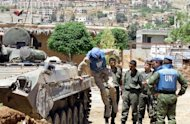 A UN monitor jumps off a tank during a visit to a military outpost at the entrance of the Syrian city of Zabadani. Syria&#39;s authorities and the opposition traded accusations Sunday over who was behind blasts that rocked Damascus and Aleppo, on the eve of parliamentary polls designed to boost the regime&#39;s legitimacy