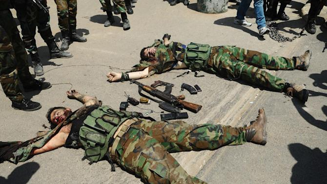 In this photo released by the Syrian official news agency SANA, bodies of fighters lie on the ground after a bombing attack in the Rokn al-Deen neighborhood, Damascus, Syria, Monday, May 4, 2015. A small group of insurgents, including a suicide bomber, carried out the attack in Damascus on Monday targeting a Syrian military logistics and supply facility, militants and activists said. (SANA via AP)