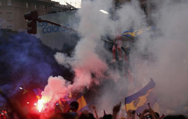A fan of Argentine soccer team Boca Juniors sits on top of traffic light post as others light flares during celebrations of Boca Juniors Fan Day in downtown Buenos Aires