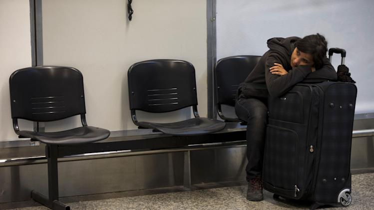 A tourist rests on her luggage as she waits at the airport during a nationwide 24-hour general strike in Buenos Aires, Argentina, Tuesday, Nov. 20, 2012. Argentine President Cristina Fernandez is facing a nationwide strike, led by union bosses who once were her most steadfast supporters. Many trains and bus lines are paralyzed; banks, courts and schools are closed; airlines have canceled flights and small groups of people have blocked highways in about a dozen places around the capital. (AP Photo/Natacha Pisarenko)