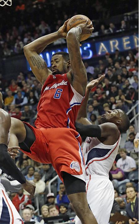 Los Angeles Clippers center DeAndre Jordan (6) pulls down a rebound in front of Atlanta Hawks point guard Shelvin Mack (8) in the second half of an NBA  basketball game Wednesday, Dec. 4, 2013, in Atl