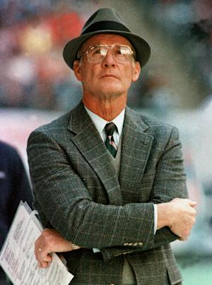 FILE - In this Dec. 18, 1988, file photo, Dallas Cowboys head coach Tom Landry watches from the sideline during an NFL football game against the Philadelphia Eagles in Irving, Texas. There are hats on the heads of more than half the coaches pictured in both NFL and college halls of fame, as well as sports coats, ties and even the occasional bow tie completing the look. Some looked so distinct _ Landry comes to mind _ that even decades later, you could identify them just by seeing their profiles. (AP Photo/Ron Heflin, File)