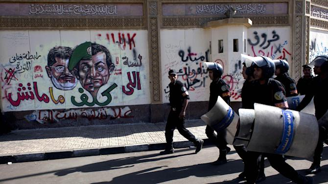 FILE - In this Saturday, Dec. 8, 2012 file photo, Egyptian riot policemen march past a mural on the wall of the presidential palace depicting president Mohammed Morsi, left, former military council ruler Hussain Tantawi, center and ousted president Mubarak with Arabic anti-Morsi graffiti, in Cairo, Egypt. Some six months since becoming the first democratically elected president of Egypt, Morsi is widely accused of having abandoned pledges of inclusive government for doctrinaire and authoritarian ways. (AP Photo/Nasser Nasser, File)