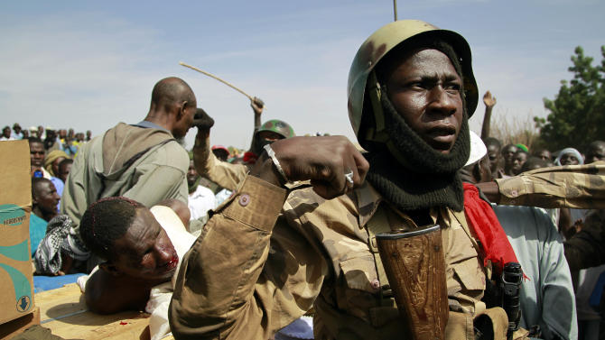 "Malian soldiers guard suspected Islamist extremists after throwing them in the back of the army truck in Gao, northern Mali, Tuesday, Jan. 29, 2013. Four suspects were arrested after being found by a youth militia calling themselves the ""Gao Patrolmen"". Malian soldiers prevented the mob from lynching them. (AP Photo/Jerome Delay)"