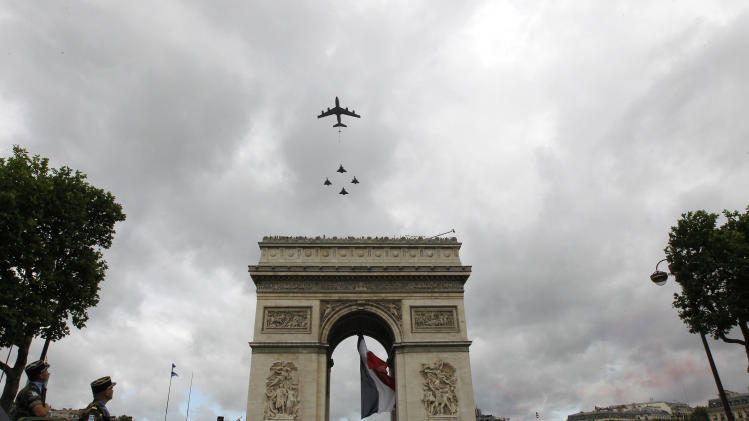 French military planes fly over the Arc de Triomphe at the start of the Bastille Day parade on the Champs Elysees avenue, Paris, Saturday, July 14, 2012. (AP Photo/Jacques Brinon, Pool)