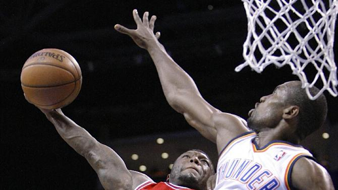 Chicago Bulls guard Nate Robinson (2) goes up for a dunk over Oklahoma City Thunder forward Serge Ibaka (9) during the second quarter of an NBA basketball game in Oklahoma City, Sunday, Feb. 24, 2013. (AP Photo/Alonzo Adams)
