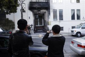 People take photographs of the damaged Chinese consulate in San Francisco