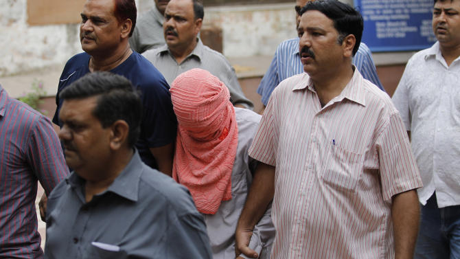 Delhi police officers escort a juvenile accused of rape, outside the Juvenile justice board in New Delhi, India, Saturday, Aug. 31, 2013. An Indian juvenile court on Saturday handed down the first conviction in the fatal gang rape of a young woman on a moving New Delhi bus, convicting the teenager of rape and murder and sentencing him to three years in a reform home, lawyers said. (AP Photo/Altaf Qadri)