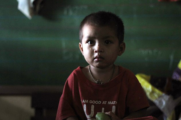 A boy waits in a temporary shelter after Typhoon Bopha made landfall in Compostela Valley in southeastern Philippines Tuesday Dec. 4, 2012. Typhoon Bopha (local name Pablo), one of the strongest typho