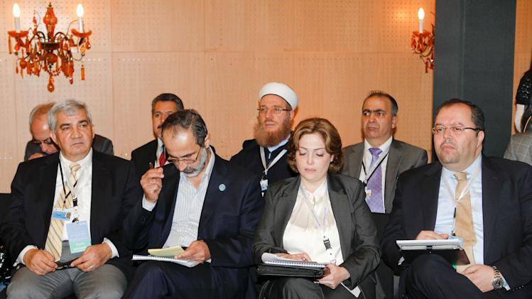 "Moaz al-Khatib, head of a new coalition of Syrian opposition groups, 2nd left, and Syrian delegation attend a meeting of the Friends of the Syrian People in Marrakech, Morocco, Wednesday Dec. 12, 2012. The Syrian opposition called for ""real support"" and not just recognition on Wednesday, hours after the U.S. declared its new coalition was the ""legitimate representative"" of its country's people. Bnner behind reads: 4th meeting of the group of ""Friends of the Syrian People"". (AP Photo/Abdeljalil Bounhar)"