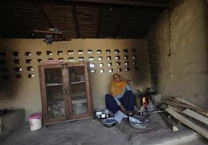 "A woman cooks ""roti"" on an earthen stove inside a farm house near the Jhajjar district"
