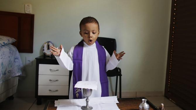 Rafael Freitas, a 3-year-old cancer patient, dresses as a priest as he performs a mass in his bedroom in Barretos