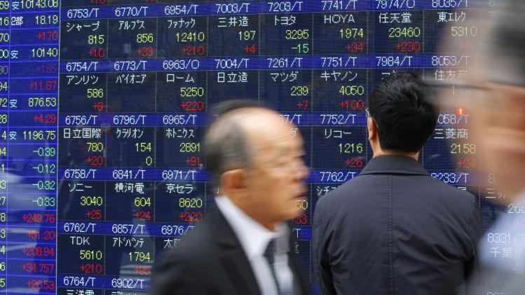 A man watches the electronic stock board of a securities firm in Tokyo, Thursday, Dec. 2, 2010. Japan's Nikkei 225 stock average surged 1.7 percent to 10,160.36, at one point hitting its highest intraday level in more than five months. (AP Photo/Shizuo Kambayashi)