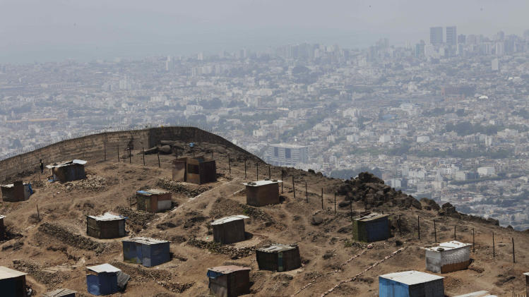 In this Nov. 26, 2012 photo, shack homes recently built on the top of a mountain overlook some of the most exclusives neighborhoods in the background, like La Molina, Miraflores, and Barrancoare, seen from the outskirts of Lima, Peru.  Seismologists, engineers and civil defense officials agree that Lima is due for an earthquake but is acutely vulnerable and sorely unprepared. More than two in five of capital residents inhabit rickety structures built on unstable, sandy soil and wetlands, which amplify a quake's destructive power, or in the hillside settlements ringing the capital that sprang up spontaneously over a generation as people fled conflict and poverty in the interior, experts say. (AP Photo/Rodrigo Abd)