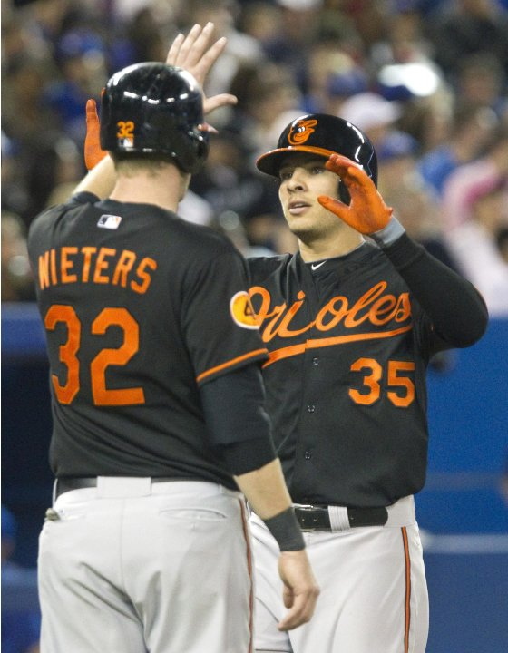 Orioles' Valencia is congratulated at home plate by teammate Wieters after he hit a two run home run against the Blue Jays in Toronto.