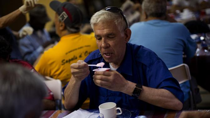 Pensioner Jose Gene Planell, 64, eats  breakfast in Caliu, a charity site in  Barcelona, Spain, Tuesday June 5, 2012. More than one hundred people are fed every day in Caliu as part of a charity program created by local volunteers and neighbors to help unemployed and people without financial resources. The Spanish economy is in recession for the second time in three years as the damage from a housing bust persists. Foreclosures are rising, Spain's banks are in worse financial shape and the government's deficit is hitting worrisome levels.  (AP Photo/Emilio Morenatti)