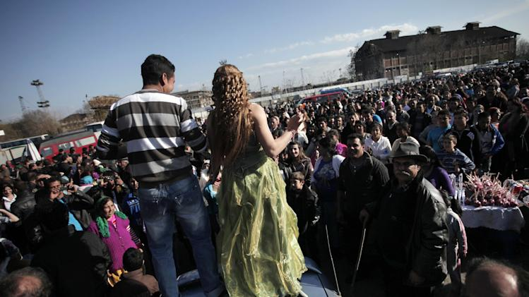 "This Saturday, March 23, 2013  photo shows people watching Roma girl and boy from the Kalaidzhi community dancing on the trunk of a car, during so called ""Roma bridal market"" . The Kalaidzhi, who represent only a small portion of the estimated 700,000 Roma in Bulgaria, are almost all devout Orthodox Christians who keep teenage boys and girls separate. Parents sometimes remove girls from school at 15 or even earlier to keep them from mixing with boys. The isolation is broken only by Internet chats and the twice-a-year bridal fairs.  (AP Photo/Valentina Petrova)"