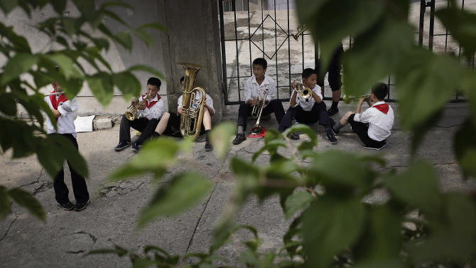North Korean students practice playing their musical instruments at the Moranbong or Moran Hill, Thursday, July 31, 2014, in Pyongyang, North Korea. Even in Pyongyang, people need a place to relax and unwind. With the heat and humidity of the Pyongyang summer now setting in, one of the most popular is Moranbong, Moran Hill, just a short walk from Pyongyang's iconic Kim Il Sung Square that is famous for its shady walking paths, vistas of the city and grassy fields. (AP Photo/Wong Maye-E)
