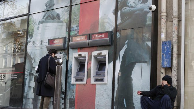 A homeless begs next to a bank of ATM's in Paris, Tuesday, Nov. 20, 2012 as France's government shrugged off the latest downgrade of its credit rating, saying Tuesday that it just needs time for reforms to the sluggish economy to take root. In a setback for President Francois Hollande's Socialist government, Moody's Investors Service stripped Europe's No. 2 economy of it of its prized AAA credit rating late Monday on concerns that its rigid labor market and exposure to Europe's financial crisis were threatening its prospects for economic growth. (AP Photo/Francois Mori)
