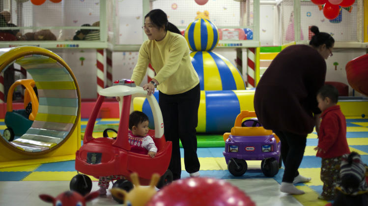 Parents play with their children at a kid's play area in a shopping mall in Beijing Thursday, Jan. 10, 2013. In China, a law generally limits urban families to having just one child. They grow up as the sole focus of doting parents. How does this affect them? What does it mean to Chinese society if generations of kids are raised this way? Authors of a new study say the one-child policy has significant ramifications for Chinese society. (AP Photo/Alexander F. Yuan)
