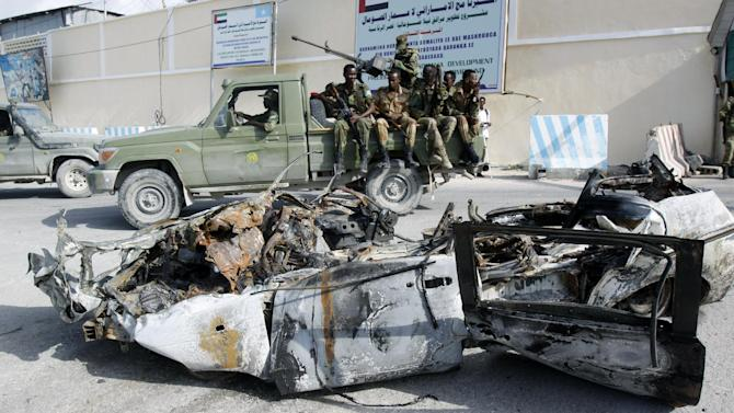 Somali soldiers sit on a pickup truck near the wreckage of a car bomb that was detonated at the main gate of the presidential palace in Mogadishu, Somalia, Wednesday, July, 9, 2014. Somali troops retook the presidential palace in the capital of Mogadishu after militants forced their way in and exchanged heavy gunfire with troops and guards Tuesday, the latest attack underscoring the threat posed by Islamic extremist group al-Shabab in east Africa. (AP Photo/Farah Abdi Warsameh)