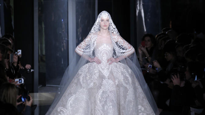 A model wears the wedding gown by Lebanese fashion designer Elie Saab for his Spring Summer 2013 Haute Couture fashion collection, presented in Paris, Wednesday, Jan.23, 2013. (AP Photo/Christophe Ena)