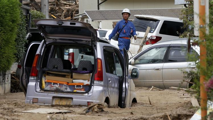 Fire fighter searches for survivors at a site where a landslide swept through a residential area at Asaminami ward in Hiroshima