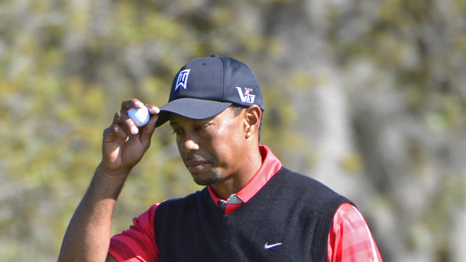 Tiger Woods holds up his ball and tips his hat to the gallery after sinking a birdie putt on the fourth hole during the final round of the Arnold Palmer Invitational golf tournament, Monday, March 25, 2013, in Orlando, Fla. (AP Photo/Phelan M. Ebenhack)