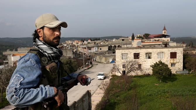 In this Thursday, Feb. 21, 2013 photo, a Free Syrian Army fighter from the Ghurabaa al-Sham brigade that holds a cluster of Christian villages stands guard on the roof top of his base, at the Christian village of Yacobiyeh, in Idlib province, Syria. Yacobiyeh and its neighbors, Judeida and Quniya, are some of the first Christian villages to be taken by the rebel Syrian Army. The rebels stormed these hilltop villages in late January, after the army used it as a base to shell nearby rebel-controlled areas. The villages are largely empty due to the fighting, with a few mostly elderly Christians -- including Roman Catholics and Armenian Orthodox _ living among Sunni Muslim refugees who have moved up here from the plains. They still face sporadic artillery bombardment from below.(AP Photo/Hussein Malla)