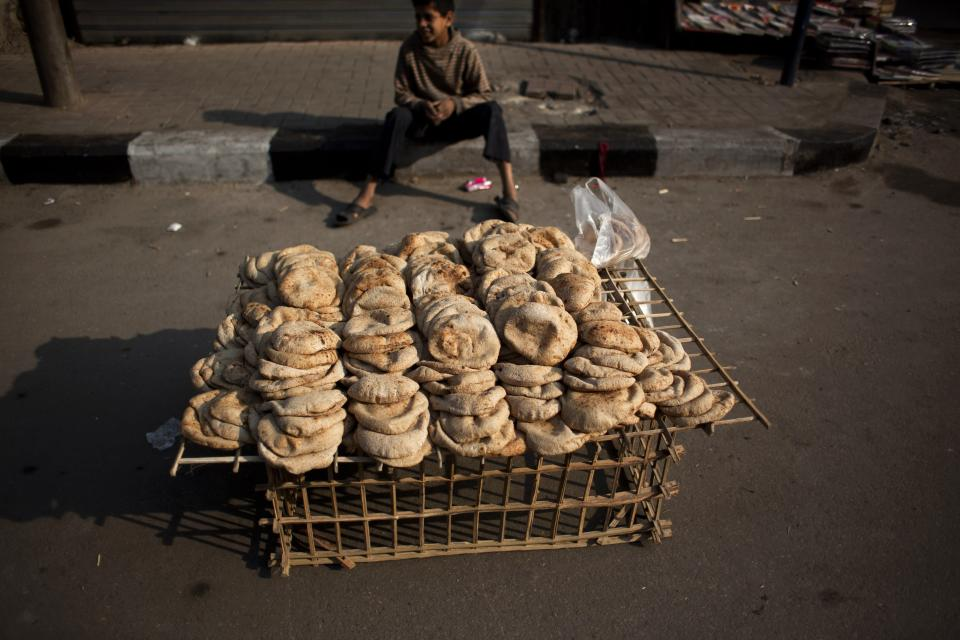 A boy sells bread in Tahrir Square, Cairo, Egypt, Monday, Feb. 14, 2011. Egypt's military rulers dissolved parliament Sunday, suspending the constitution and promising elections in moves cautiously welcomed by pro-democracy protesters. (AP Photo/Emilio Morenatti)