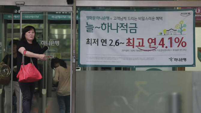 "A woman walks past an advertisement for a bank's interest rate in Seoul, South Korea, Thursday, Aug. 14, 2014. South Korea's central bank, Bank of Korea, cut its key interest rate for the first time in 15 months on Thursday, providing support to an economy dragged down by the shock of a ferry sinking that killed hundreds of teenagers. The banner reads: ""Deposit interest, the lowest 2.6 percent - the highest 4.1 percent."" (AP Photo/Ahn Young-joon)"