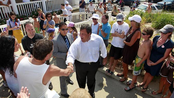 """New Jersey Gov. Chris Christie, center, greets supporters in Manasquan, N.J., Monday, July, 16, 2012. Later at a beach pavilion, Christie told residents to tell state Senate President Steve Sweeney and Assembly Speaker Sheila Oliver to """"pass my taxcut now."""" The Republican has promised to spend the summer holding public forums to bash Democratic lawmakers, who he says are blocking tax breaks. (AP Photo/Mel Evans)"""
