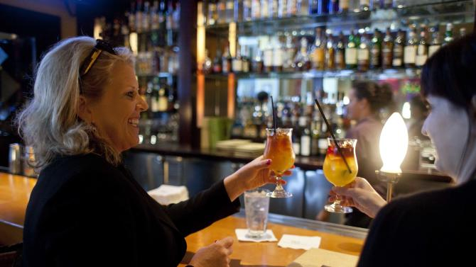 In this photo taken Monday, Aug. 6, 2012, Melissa Fullerton, left, of Highland Village, Tex., raises her $5 Mai Tai during happy hour at the Roy's restaurant in San Francisco. The concept of happy hour when bars offer lower prices or two-for-one specials seems like a widespread tradition, but is actually illegal or restricted in quite a few places. (AP Photo/Eric Risberg)