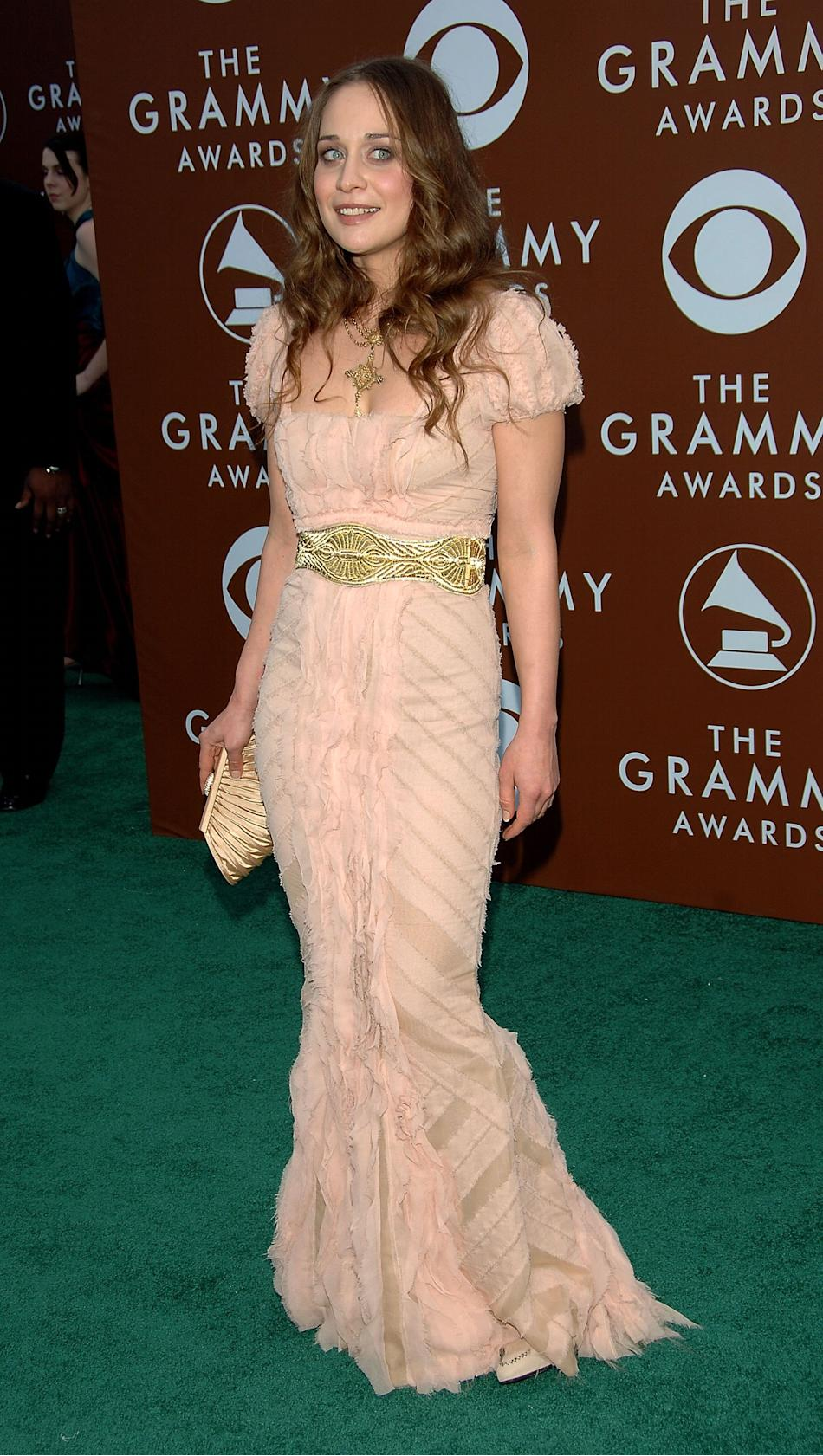 At the 2006 GRAMMYs, Fiona pulled off an ethereal gothic mermaid vibe in a floor-length unfinished gown with intricate gold accessories, earth-tone make-up and soft waves. (Photo by Kevin Mazur/WireIm