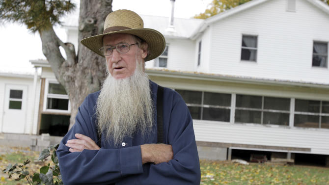 FILE - In this Monday, Oct. 10, 2011 file photo, Sam Mullet stands in front of his Bergholz, Ohio, home. Attorneys for a group of Amish men and women found guilty of hate crimes for cutting the hair and beards of fellow members of their faith in eastern Ohio are arguing that the group's conviction, sentencing and imprisonment in separate facilities across the country violates their constitutional rights and amounts to cruel and unusual punishment, according to recent court filings. The Amish group's leader, Mullet, was sentenced to 15 years in prison, while the rest of the group got sentences ranging from one to seven years. (AP Photo/Amy Sancetta, File)