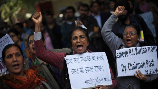 Protesters hold placards near Indian parliament to protest a new sexual violence law as the parliament convenes in New Delhi, India, Thursday, Feb. 21, 2013.  Activists say the law is inadequate and it only partially followed the recommendations of a government panel set up after the fatal gang rape of a woman in New Delhi which led to nation-wide protests. The placards demand the removal of Indian Parliament's upper house's Deputy Chairman, P.J.Kurien who is facing rape allegations. (AP Photo/Altaf Qadri)
