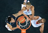 Argentinian guard Carlos Delfino (L) vies with French forward Nicolas Batum and French guard Tony Parker (R) during the Men&#39;s preliminary round group A basketball match of the London 2012 Olympic Games France vs Argentina at the basketball arena in London. France won 71 to 64