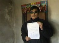Still image taken from video shows blind legal activist Chen Guangcheng holding a petition in his village home in Linyi in eastern Shandong province