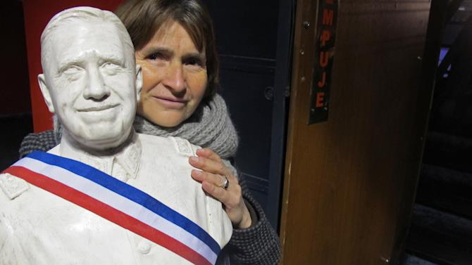 Maria Cristina Osorio, a 57-year-old retired nurse, walks into a downtown Santiago theater for the screening of a documentary on Gen. Augusto Pinochet carrying a bust of the former strongman in Santiago, Chile, Sunday June 10, 2012. The film casts Pinochet as a national hero who saved Chile from communism and who died victimized by  leftists who accused him of embezzlement and human rights crimes.(AP Photo/Luis Henao)