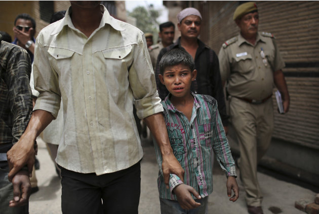 A young Indian bonded child laborer cries as he is walked away after being rescued during a raid by workers from Bachpan Bachao Andolan, or Save the Childhood Movement, at a garment factory in New Del