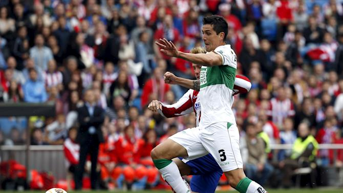 Atletico Madrid's Torres fights for the ball with Elche's Roco during their Spanish first division soccer match at Vicente Calderon stadium in Madrid
