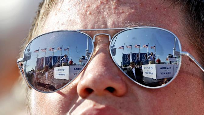 Republican presidential candidate, former Massachusetts Gov. Mitt Romney, left, and vice presidential candidate, Rep. Paul Ryan, R-Wis., are seen reflected in a supporters' sunglasses at a campaign event, Saturday, Sept. 1, 2012, in Jacksonville, Fla.  (AP Photo/Mary Altaffer)