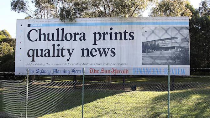 A billboard advertising Fairfax Printing House and the town of Chullora stands outside Fairfax Printers in the outer suburb of Chullora in Sydney, Australia,  Monday, June 18, 2012. Australian publisher Fairfax Media Ltd. said Monday it will shed 1,900 jobs over three years and erect pay walls for two flagship newspapers as readers increasingly move online. Australia's largest newspaper publisher after News Corp. also said it would close the printing plant in Sydney as well as plants in Melbourne by June 2014. (AP Photo/Rob Griffith)