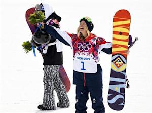Third placed Britain's Jones gestures during flower ceremony after competing in the women's snowboard slopestyle finals event at the 2014 Sochi Winter Olympics in Rosa Khutor