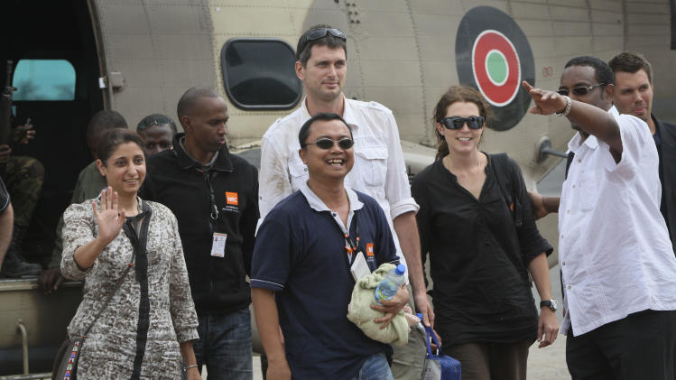 Released aid workers Horat Sadosay, 38, a Canadian citizen of Pakistani origin, left, Glenn Costes of the Philippines, 40, center, Steven Dennis of Canada, 37, above-center, and Astrid Sehl of Norway, 33, center-right, arrive back by Kenyan military helicopter at Wilson airport in Nairobi, Kenya Monday, July 2, 2012. A pro-government Somali militia group said Monday that it rescued the four aid workers kidnapped by gunmen from a refugee camp in Kenya last week. (AP Photo/Sayyid Azim)