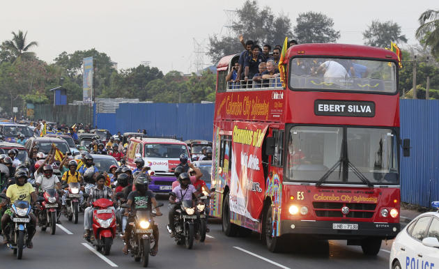 Sri Lankan cricket fans rally with players' bus as they return from Bangladesh after winning the Asia Cup in Colombo, Sri Lanka, Sunday, March 9, 2014. Sri Lanka Saturday won the cricket tournamen