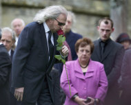 Barry Gibb kisses a rose in farewell to his brother Robin Gibb at the graveside at St Mary's Church in Thame, England, Friday, June 8, 2012. Robin Gibb a member of the iconic Bee Gees pop group died May 20, after a long battle with cancer.(AP Photo/Alastair Grant)